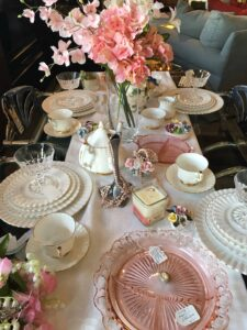 A beautiful tablescape featuring vintage china, hand-poured candles, freshwater pearls, silk flowers, silver plate candlesticks and depression glass. All currently in store.
